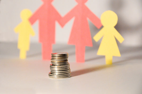 paper cut-outs of family with coins- financially support family concept